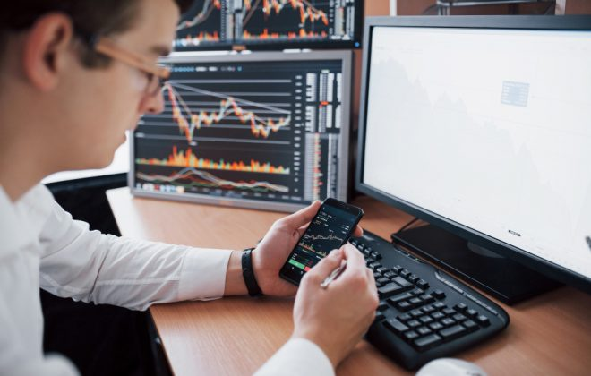 Over the shoulder view of and stock broker trading online while accepting orders by phone. multiple computer screens ful of charts and data analyses in background Free Photo